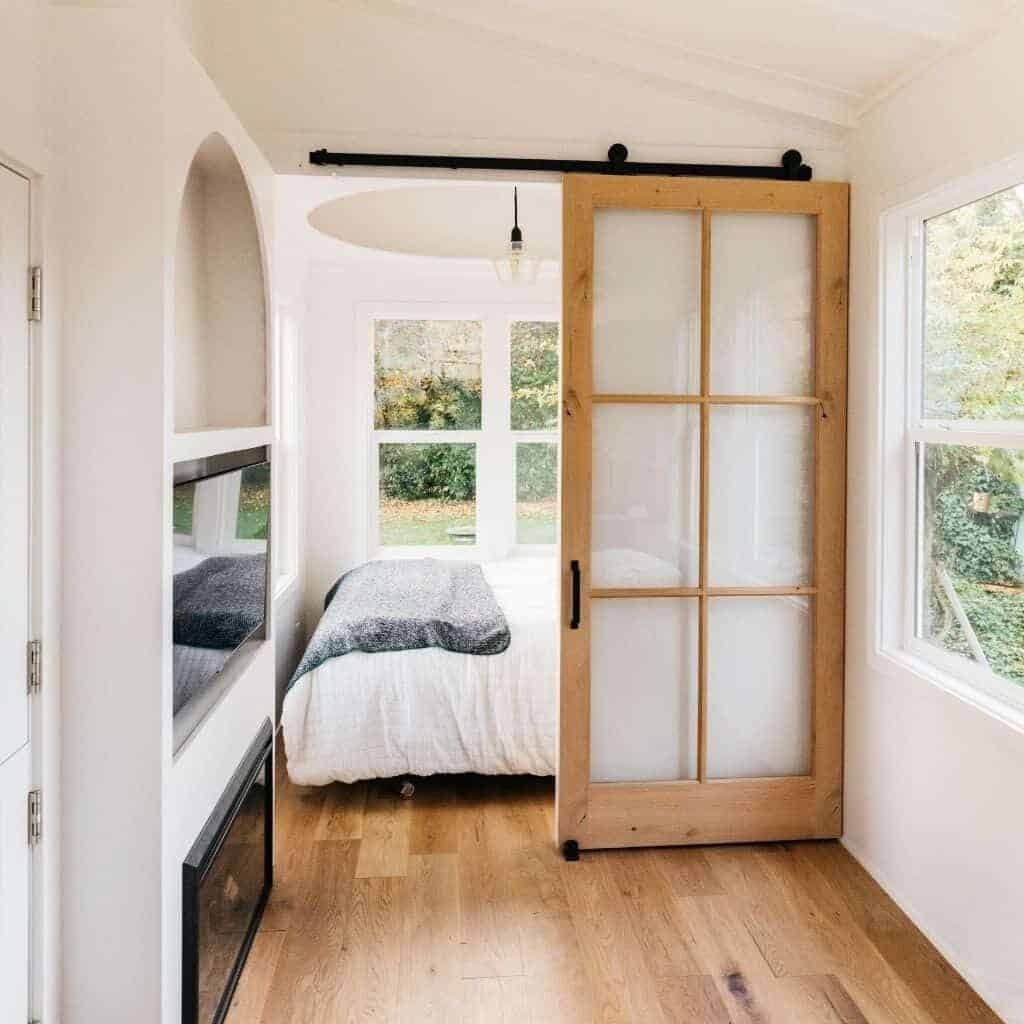 Bedroom in a tiny house with a barn door.