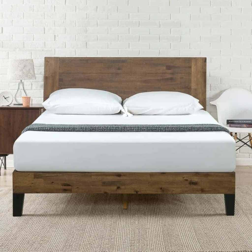 Wooden platform bed in front of a white brick wall.