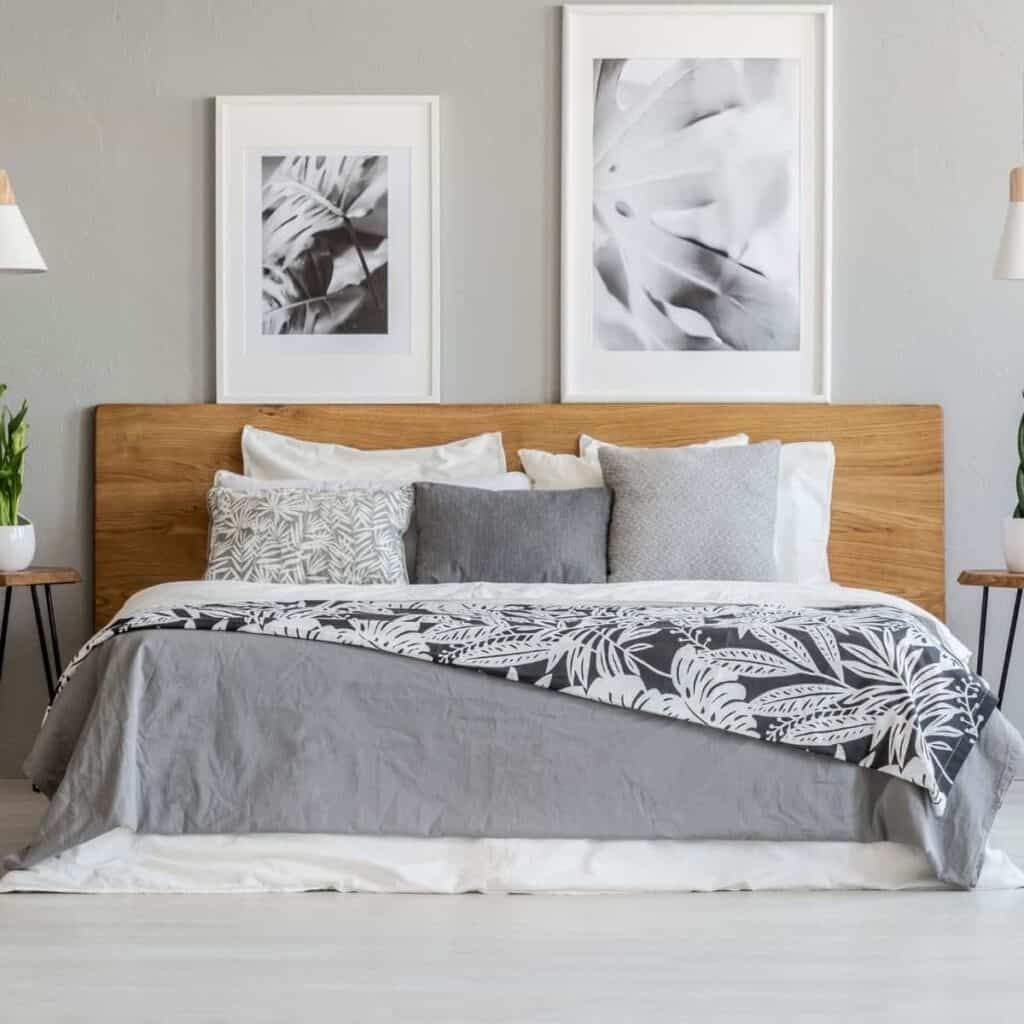 Wooden platform bed in a bedroom with art on the wall.