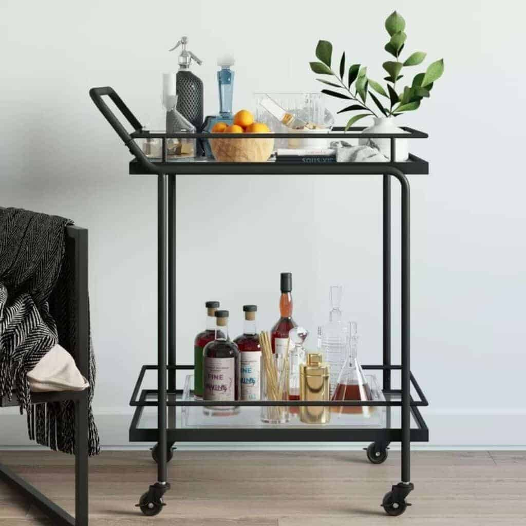 Black metal bar cart and glass shelves with drinks and a plant on it.