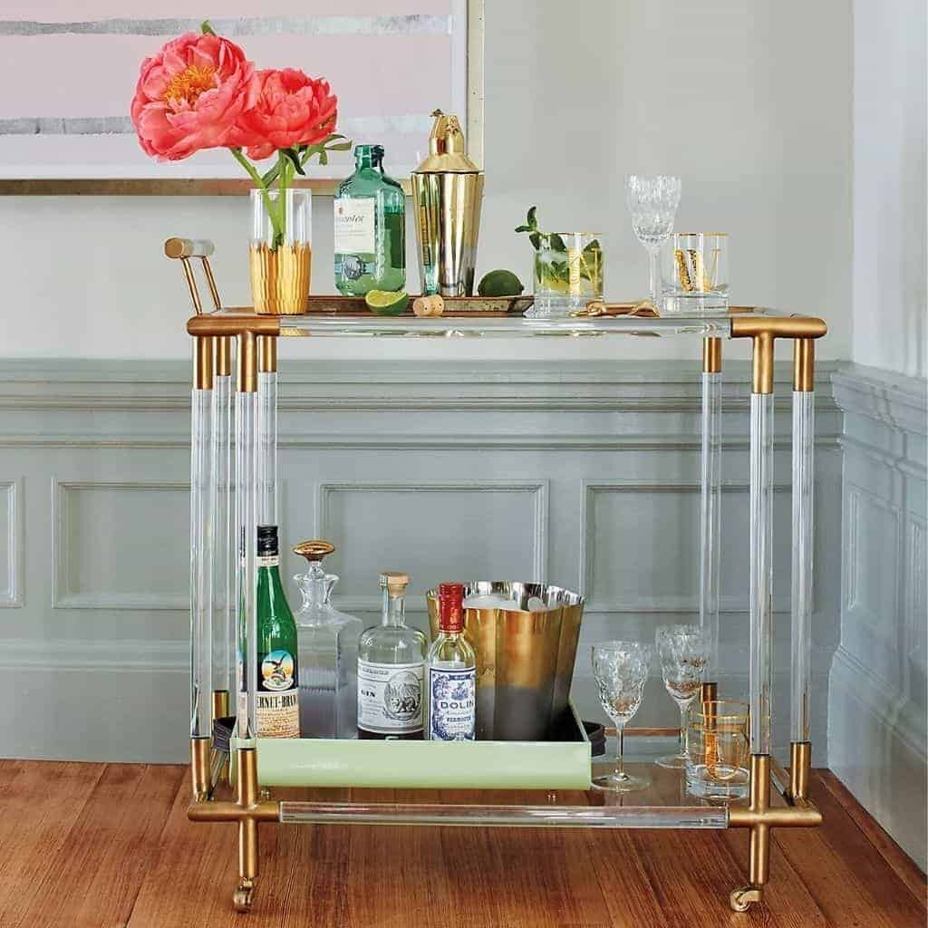 Brass and glass bar cart with drinks and flowers on it.