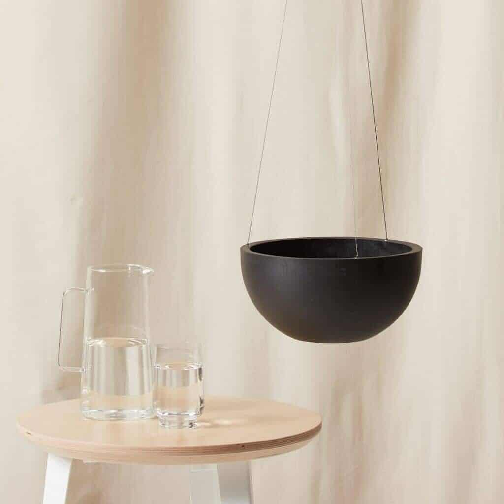 Charcoal plastic hanging planter next to a table with glasses of water.