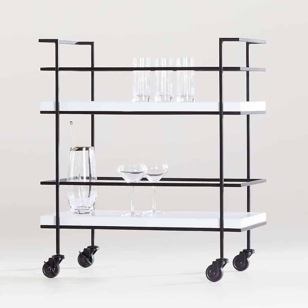 Glasses on a black and white bar cart.