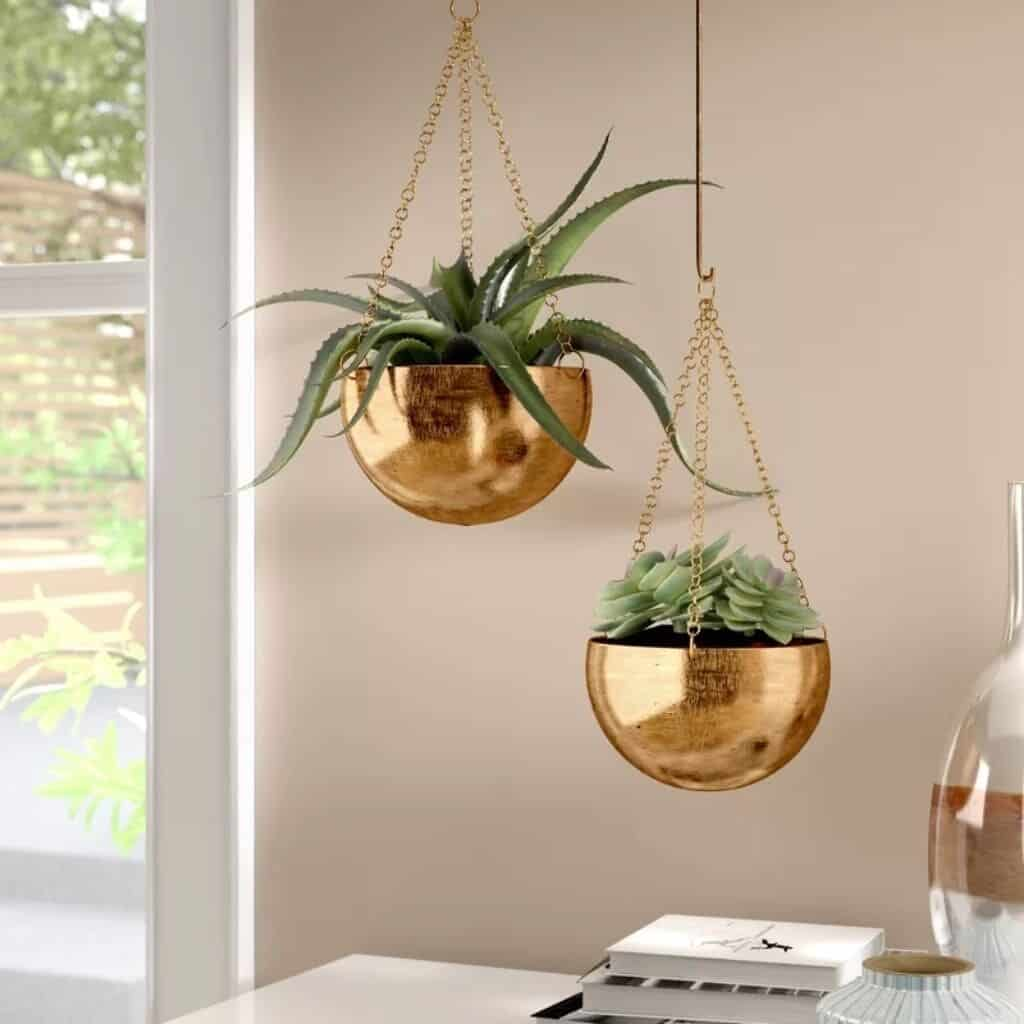 Gold planters above a table in a room.
