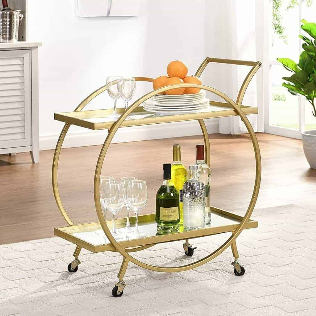 Gold metal round bar cart with drinks and plates on it.