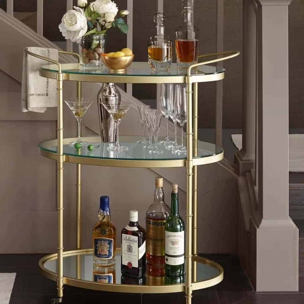 Gold three-tier round bar cart with drinks on it.