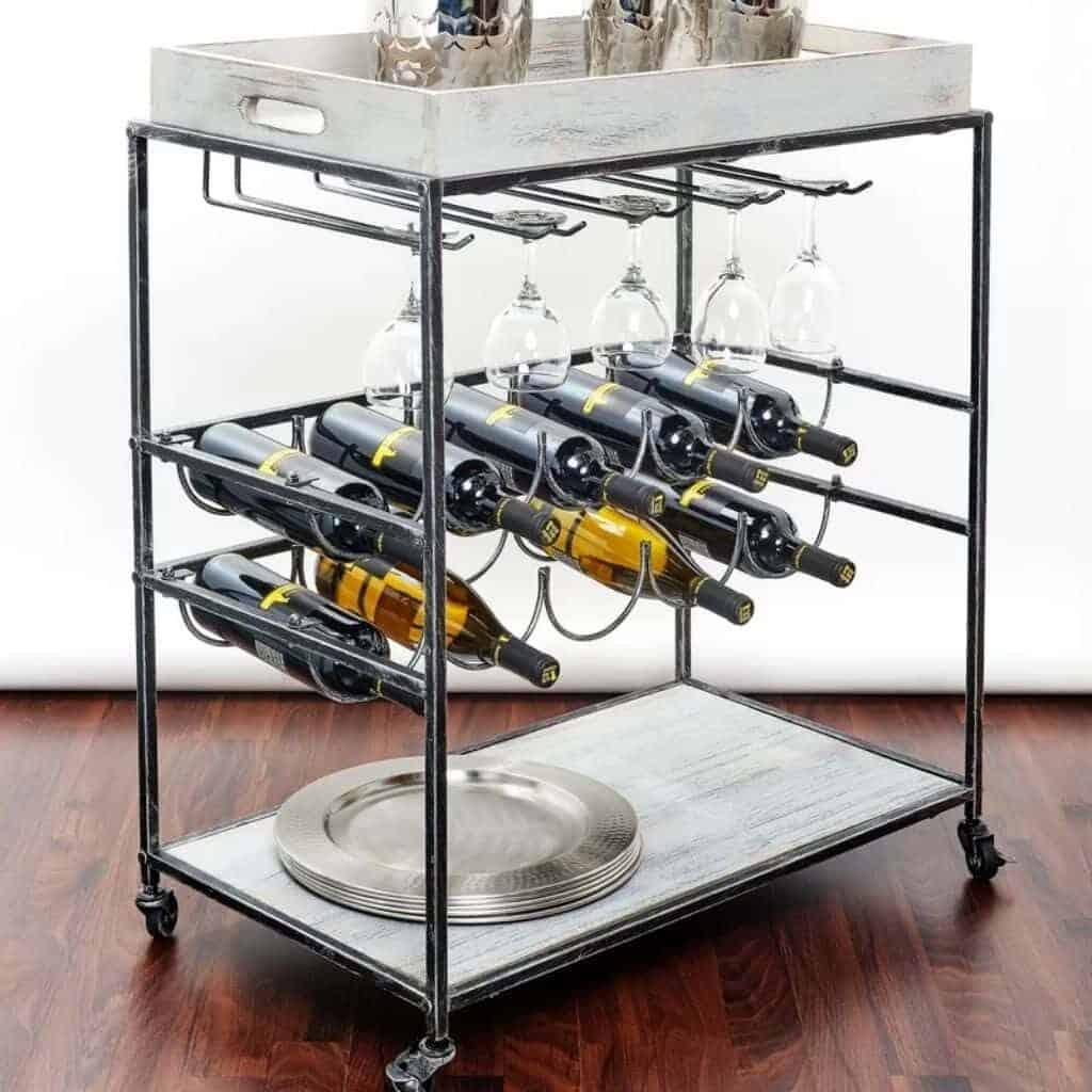 Metal bar cart with light wood shelves holding wine bottles and glasses.