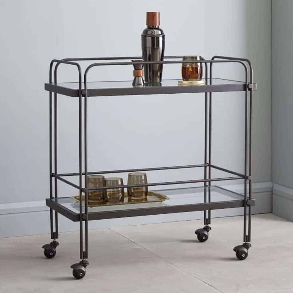 Metal bar cart with glass shelves and drinks on it.