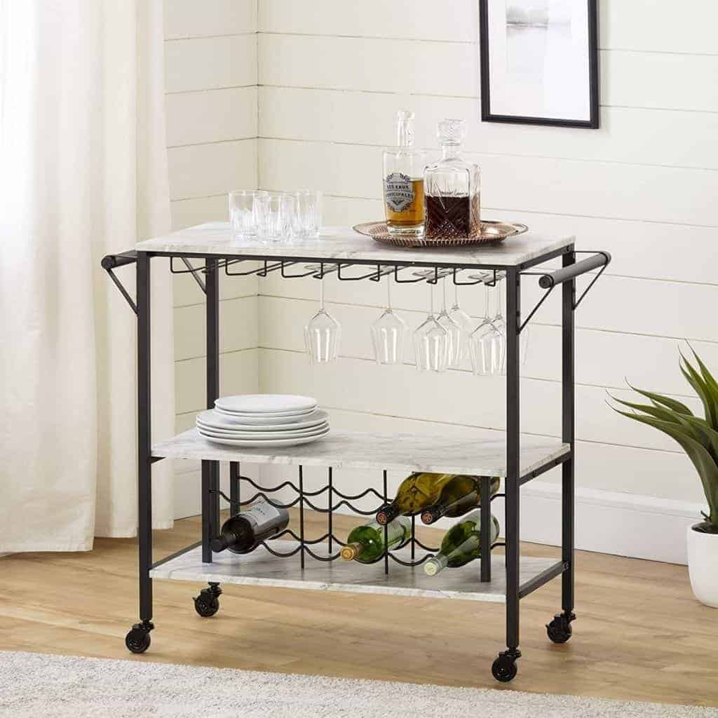 Bar cart with a metal frame and marble shelves holding plates and wine.