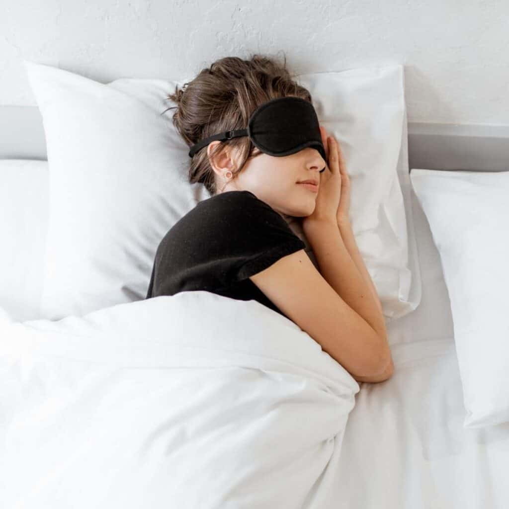 Person sleeping in a bed and wearing an eye mask.