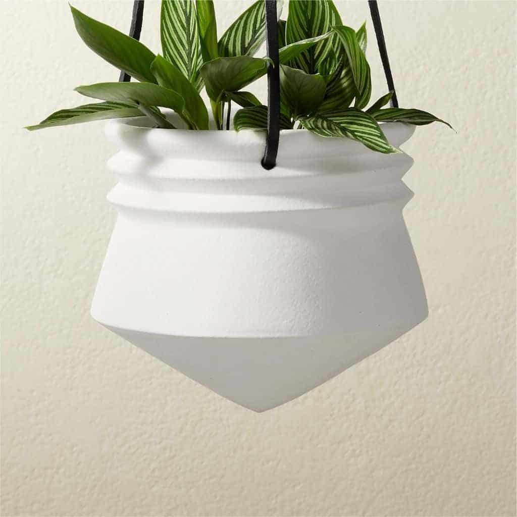 White stone pointed hanging planter with a leather rope.