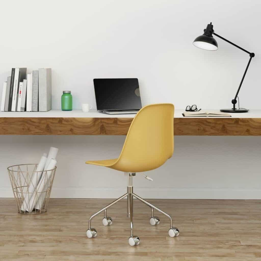 A desk against a wall with a rolling chair next to it.