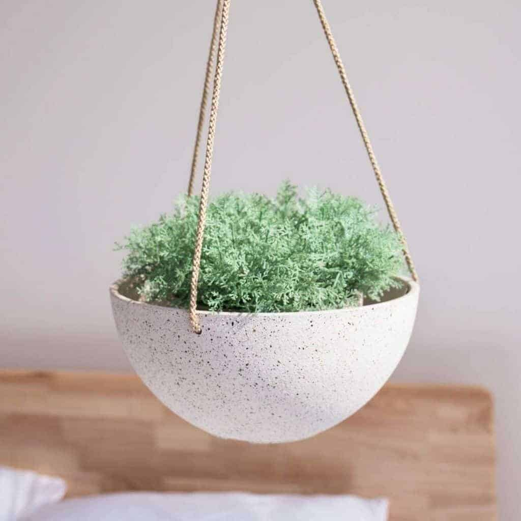 White speckled hanging planter in a bedroom.